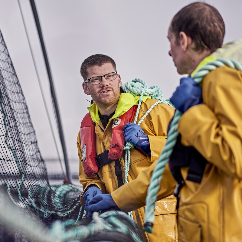 Cooke staff on boat with rigging in background in waterproofs